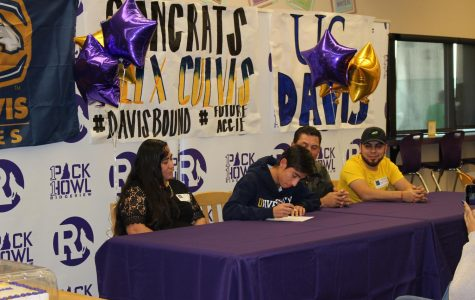 Alex Cuevas signs his letter of intent to UC Davis as his family looks on.