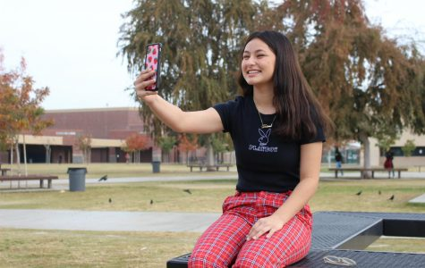 Desiree Machado also known as Dez Machado poses with her cell phone.