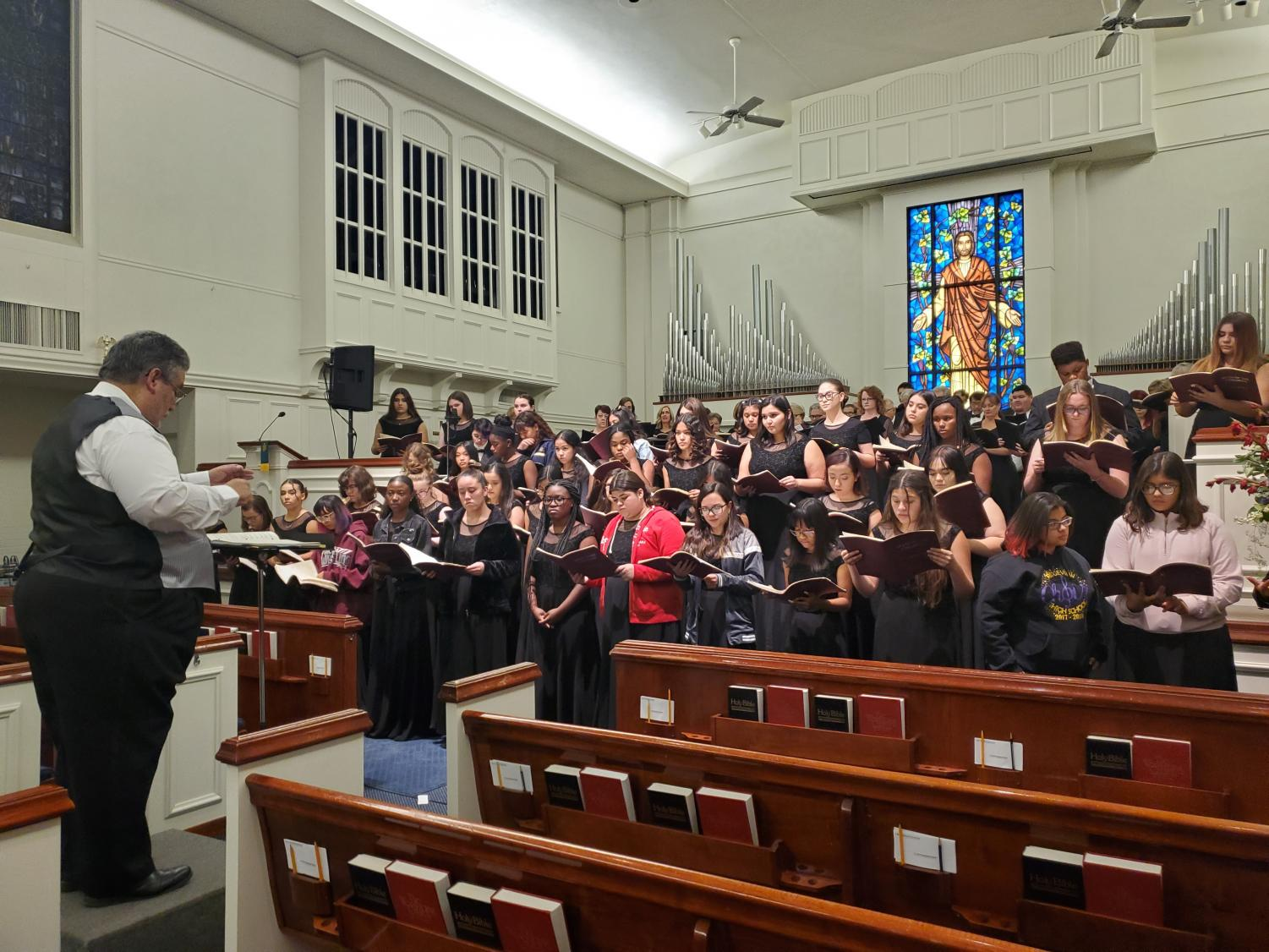 Ridgeview choir students gathering at a church to practice the song they will be performing with director of the Master Chorale, Robert Provencio.