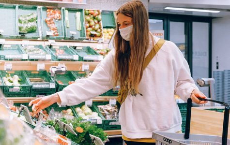 A young women standing in front of the vegetable section in today's world.