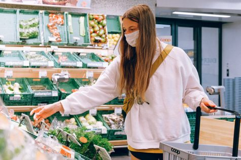 A young women standing in front of the vegetable section in today