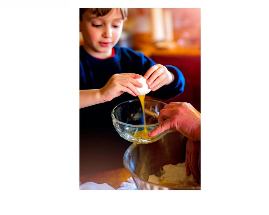 A+young+boy+is+learning+how+to+make+eggs+with+the+help+of+his+teacher.