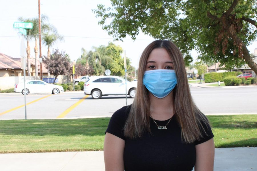 A Ridgeview High School student poses with mask in front of school.