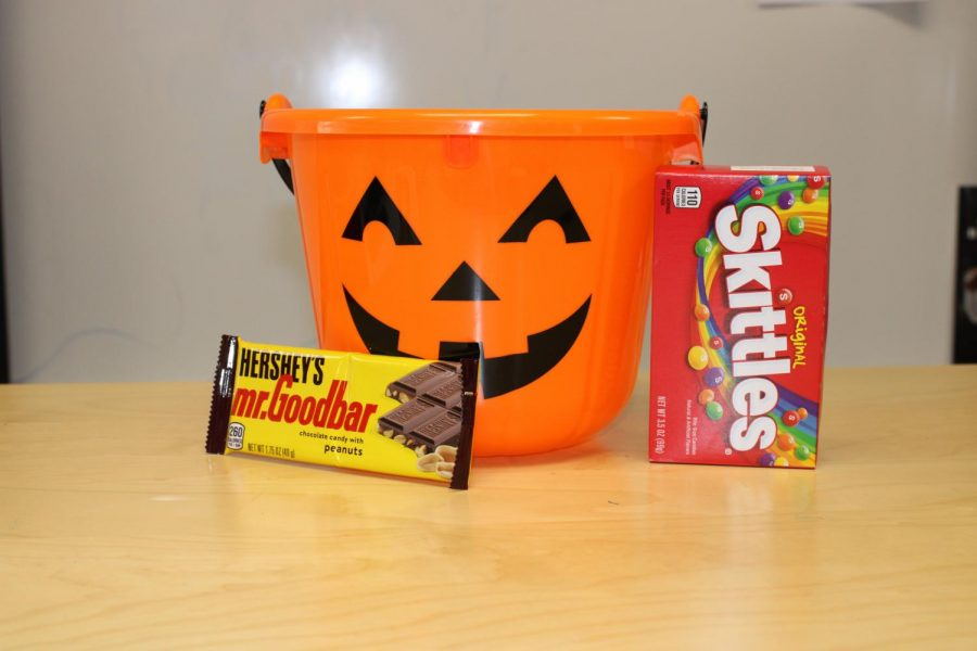 A trick or treat bucket next  to a Mr. Goodbar and a box of Skittles.